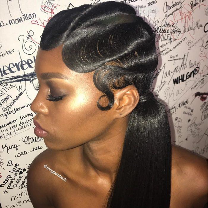 Chica afroamericana con peinado de cola de caballo hacia un lado y ondulaciones en el cabello