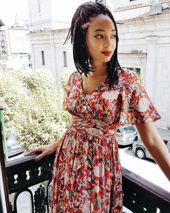 Chica afroamericana con peinado de trenzas hasta los hombros y con vestido floreado