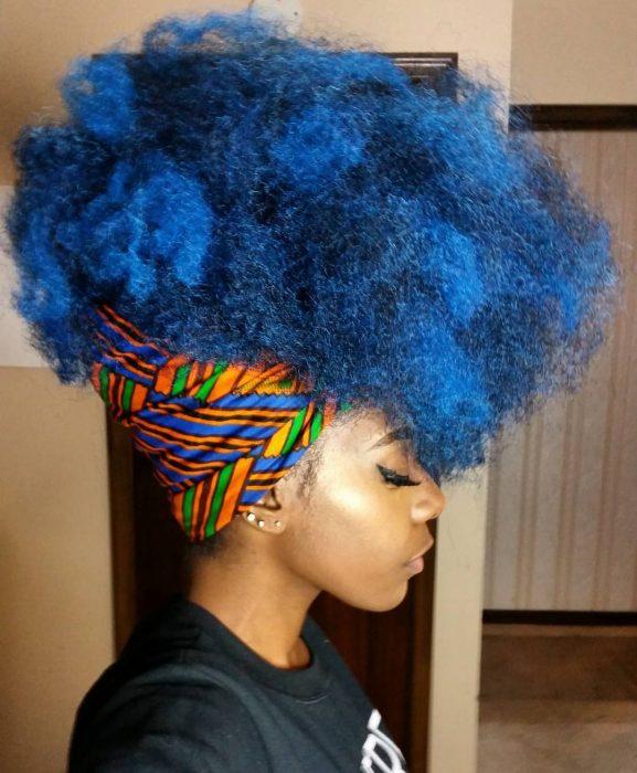 Chica afroamericana con cabello chino, esponjado, de color azul, peinado con una bandana o paliacate