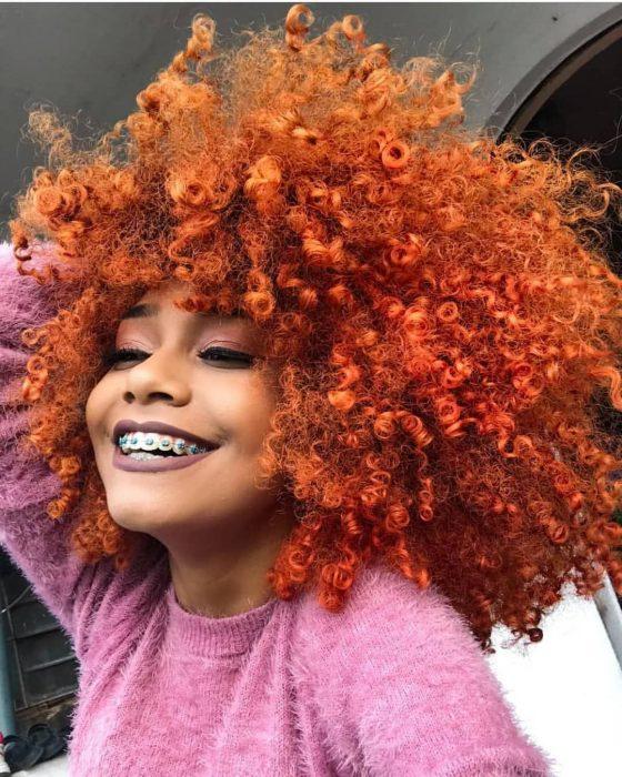 Chica afroamericana con cabello chino afro teñido de anaranjado, con brackets