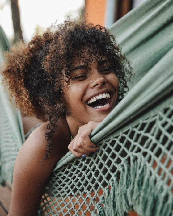 Chica afroamericana de cabello café y chino, riéndose en hamaca