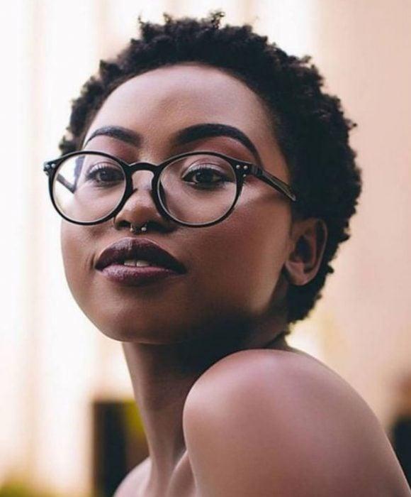 Chica afroamericana de piel morena, con lentes, cabello corto y afro con piercing en el septum
