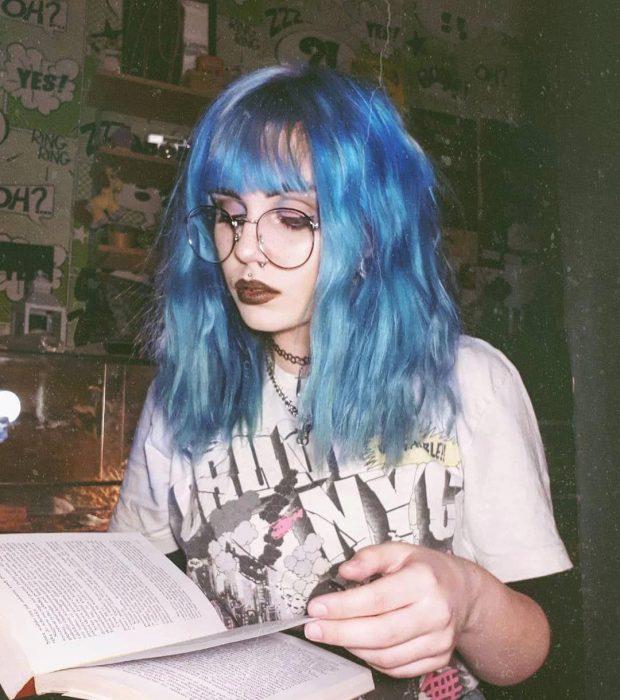 Chica de lentes redondos vintage, con cabello mediano y fleco; color azul