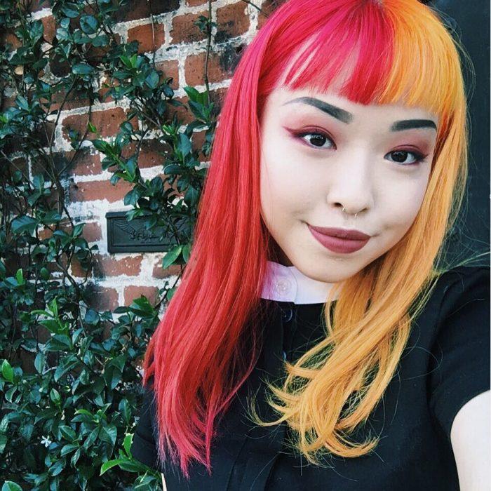Chica coreana de cabello teñido de dos colores: rosa y anaranjado