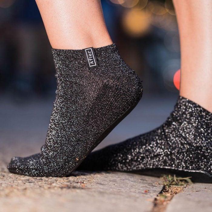 Mujer usando unos calcetines de color negro con brillos diseñados exclusivamente para caminar después de quitarte los tacones