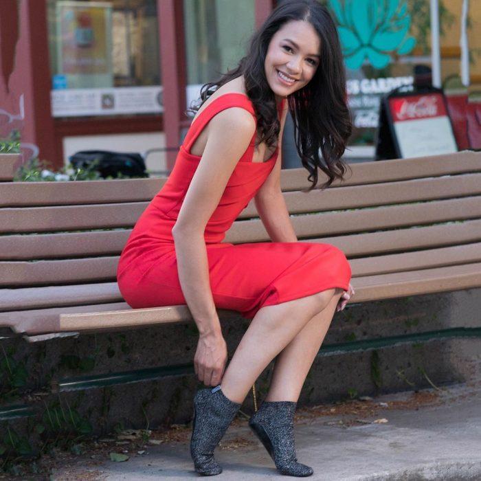 Chica usando un vestido rojo con unos calcetines de color negro diseñados especialmente para caminar por la calle después de bailar