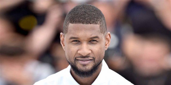 Usher con camisa blanco, mirando al frente en una alfombra roja