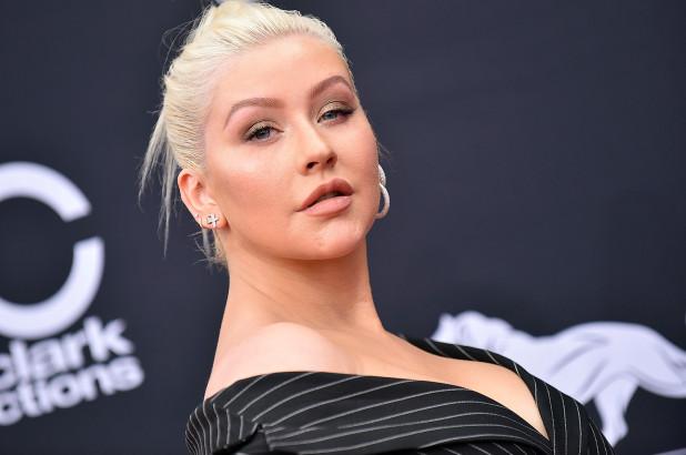 Christina Aguilera mirando ligramente hacia arriba, pasando por una alfombra roja