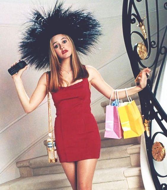 Cher de Clueless usando un vestido de color rojo mientras baja por las escaleras de su casa. Trae puesto un sombrero de plumas y está cargando bolsas de ropa en sus manos