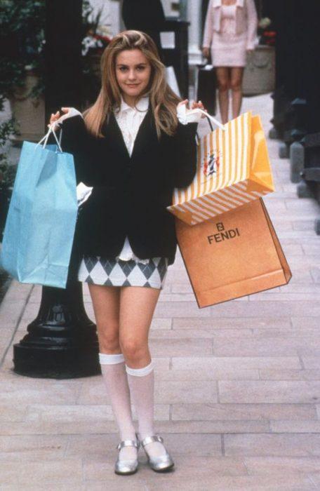Cher de Clueless usando una falda de rombos, saco negro y calcetas blancas mientras va de compras