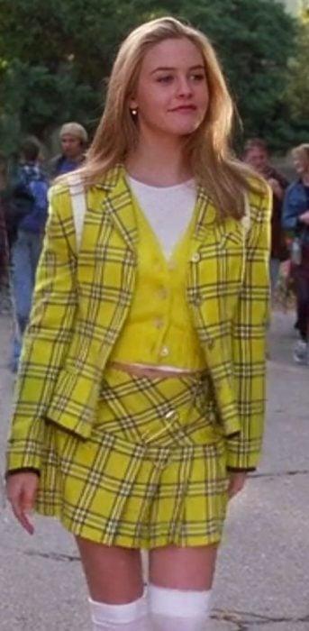 Cher de Clueless vistiendo su traje amarillo de sastre de cuadros con calcetas blancas y blusa amarilla