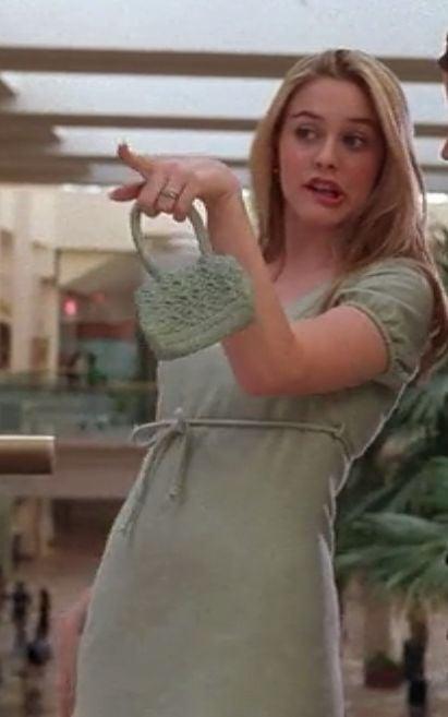 Cher de Clueles usando un vestido verde menta corto con una bolsa a juego