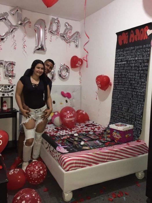 Pareja de novios en una habitación decorada con globos, petalos de rosa y pancartas para celebrar su primer día de novios