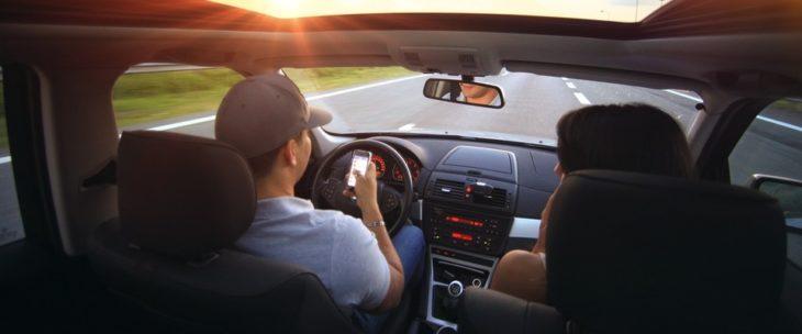 Hombre y mujer dentro de un automóvil leyendo un mensaje