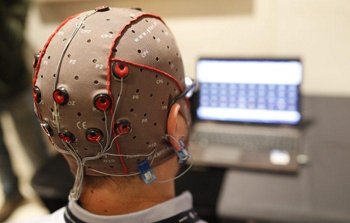 la cabeza de un hombre vista de atrás con una gorra y electrodos conectados y un monitor al frente