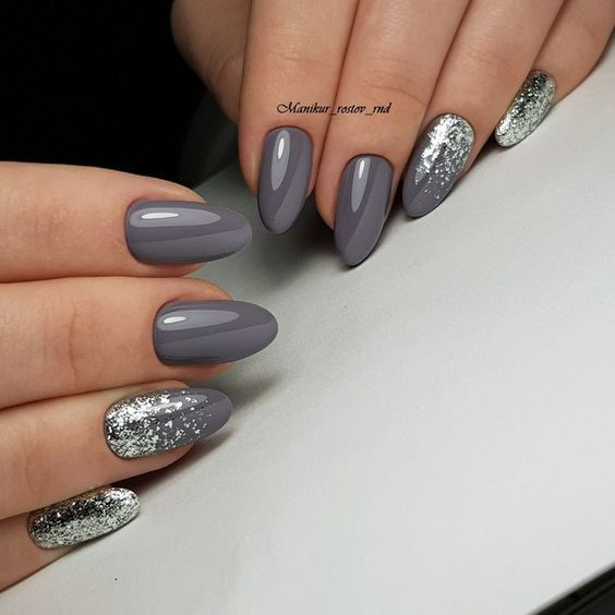 Manos de una mujer con las uñas pintadas de color gris con brillos