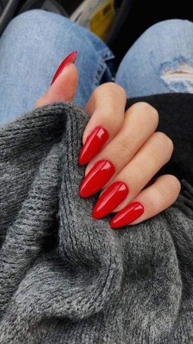 Manos de una mujer con las uñas pintadas de color rojo