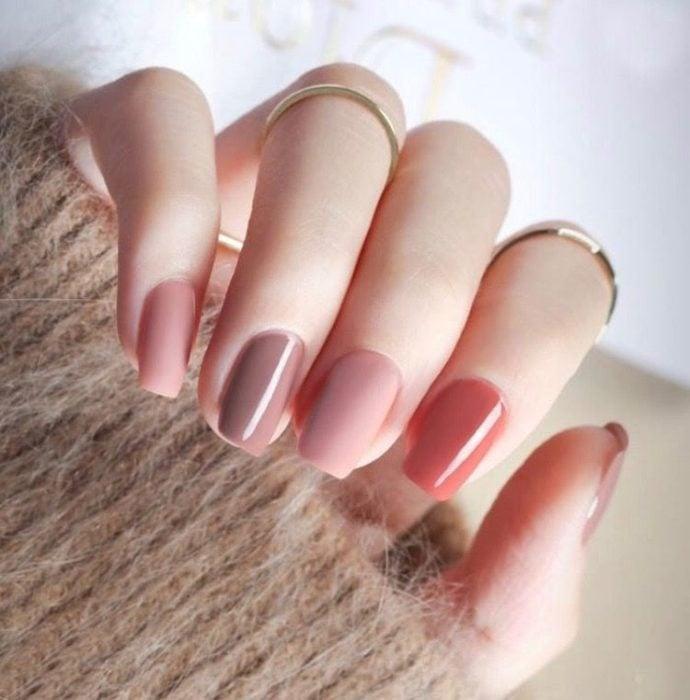 Manos de una mujer con las uñas pintadas en colores neutros