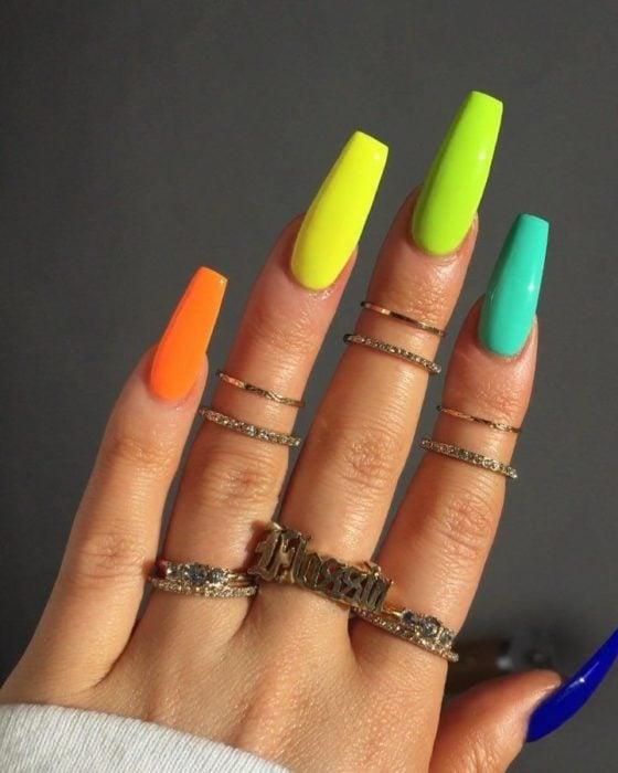 Manos de una mujer con las uñas pintadas en colores neón en amarillo, naranja y verde