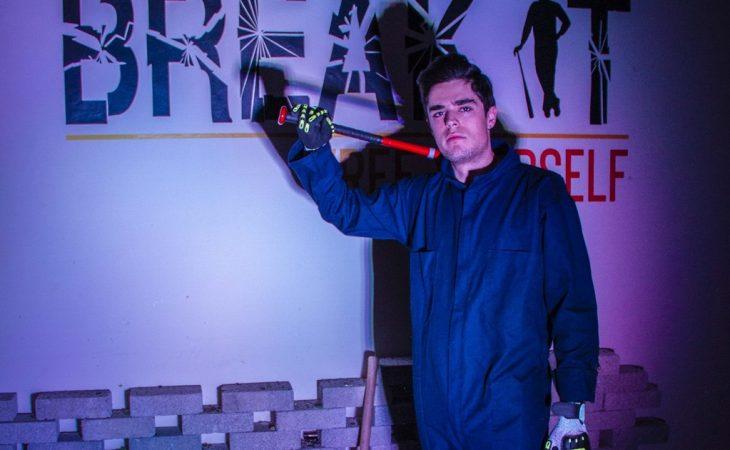 un joven con traje de seguridad y un bate posa a un lado del logotipo de Break It