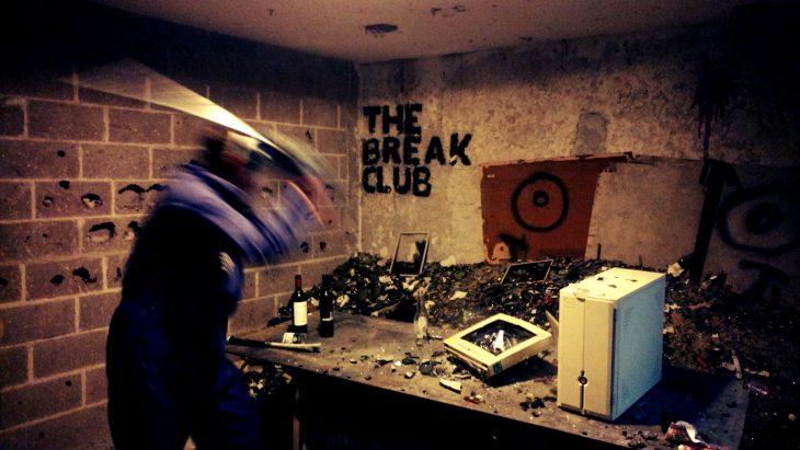 un hombre golpea artículos electrónicos sobre una mesa, en la pared un letrero dice The Break Club