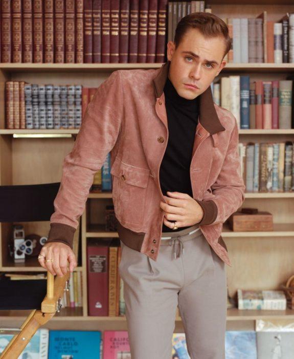 Fotos de Dacre Montgomery con abrigo rosa en una biblioteca