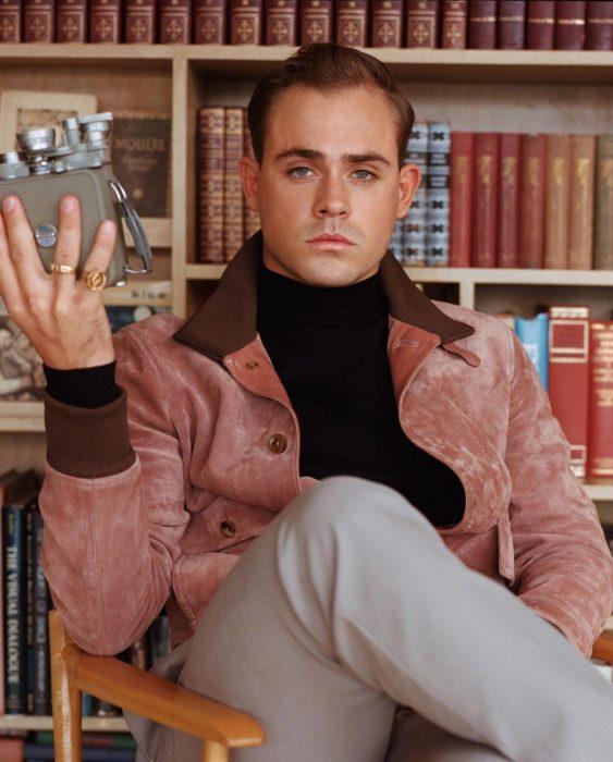 Actor Dacre Montgomery sentado en una biblioteca con saco rosa