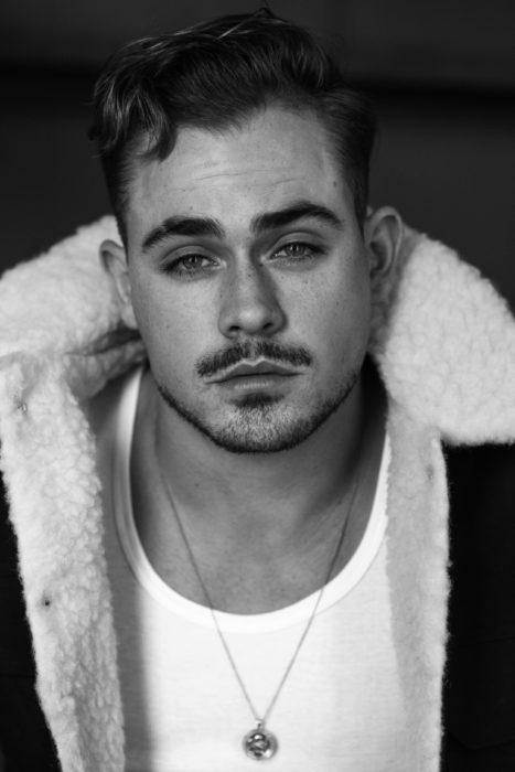 Fotos de Dacre Montgomery con abrigo y bigote, fotografía en blanco y negro