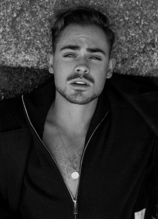 Fotos de Dacre Montgomery acostado, con bigote; fotografía en blanco y negro