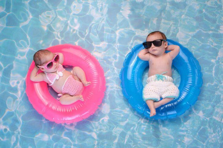 una toma aérea de un niño y una niña en una alberca cada uno con un salvavidas, ella con uno rosa y él con uno azul