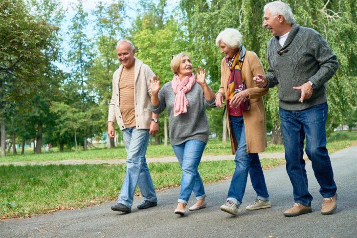 cuatro adultos mayores, dos mujeres y dos hombres caminando por un parque y hablando