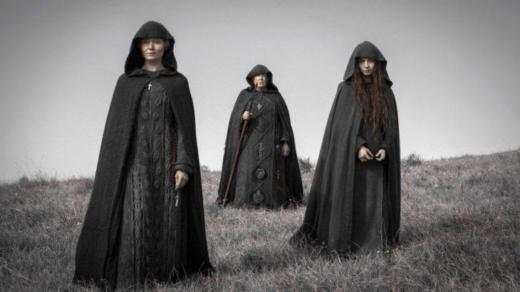Grupo de personas con capucha, escena serie Lambs of God
