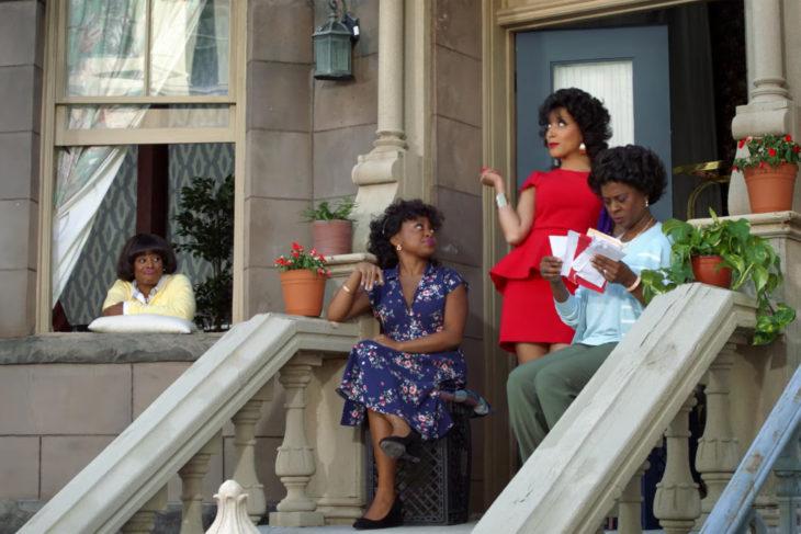 Grupo de mujeres reunidas frente al portico en unas escaleras, escena de la serie A Black Lady Sketch Show