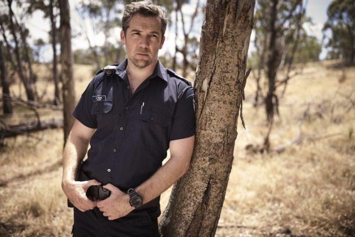 Hombre con traje de policía recargado en un árbol, escena de la serie Glitch