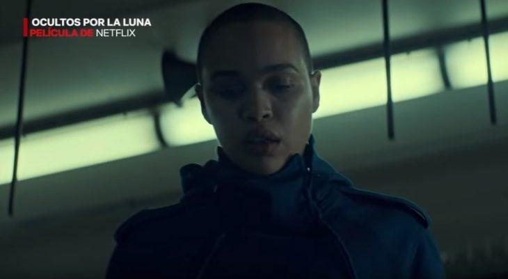 Mujer sin cabello mirando hacia abajo, escena de la película Ocultos por la Luna