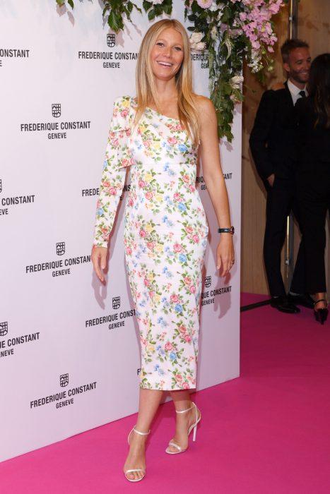 Gwyneth Paltrow en una alfombra rosa modelando un vestido a flores