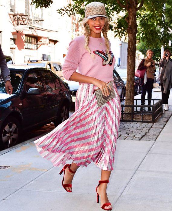 Beyoncé sonriendo y modelando un outfit en color rosa