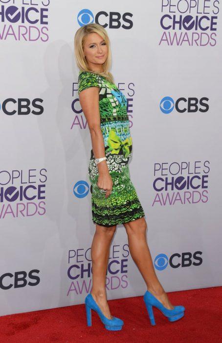 Paris Hilton en una alfombra roja modelando sus zapatos azules