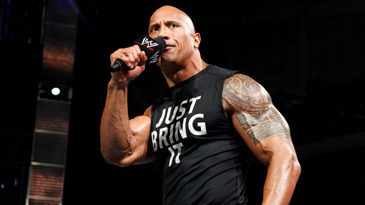 Dwayne Jonhson en camiseta negra con letras blancas y sosteniendo un micrófono de la WWE