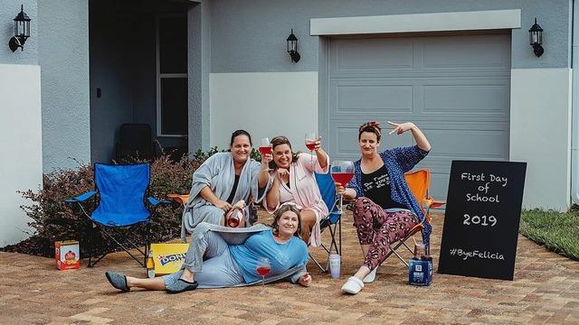 Grupo de madres sosteniendo un par de copas de vino tino en sus manos celebrando el regreso a clases de sus hijos, fotografía tomada por Shawna