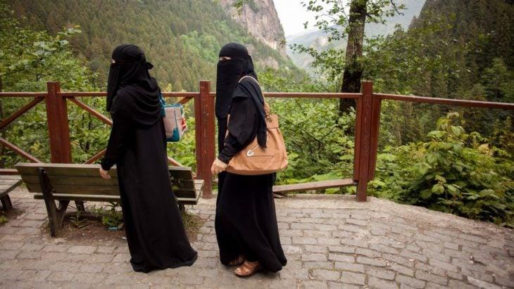 dos mujeres árabes caminan por un espacio abierto en un parque, se observa flora y una montaña