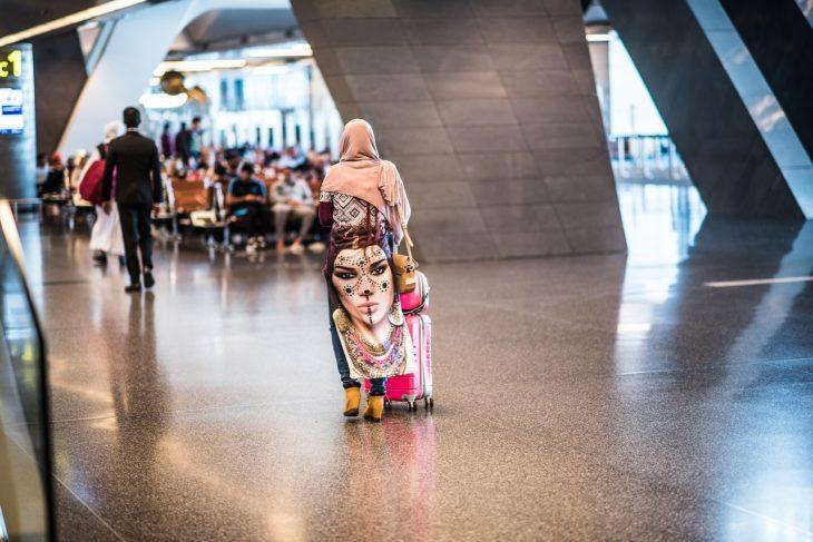 toma de espaldas de una mujer árabe que camina por un aeropuerto