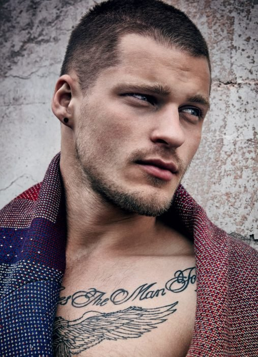 Hombre ruso guapo con cabello rapado y tatuaje en el pecho