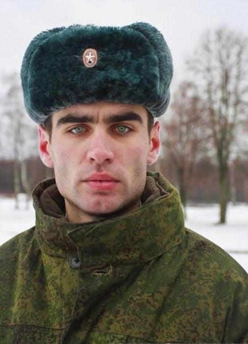 Hombre ruso guapo con gorro para el frío y chamarra militar, de ojos verde claro