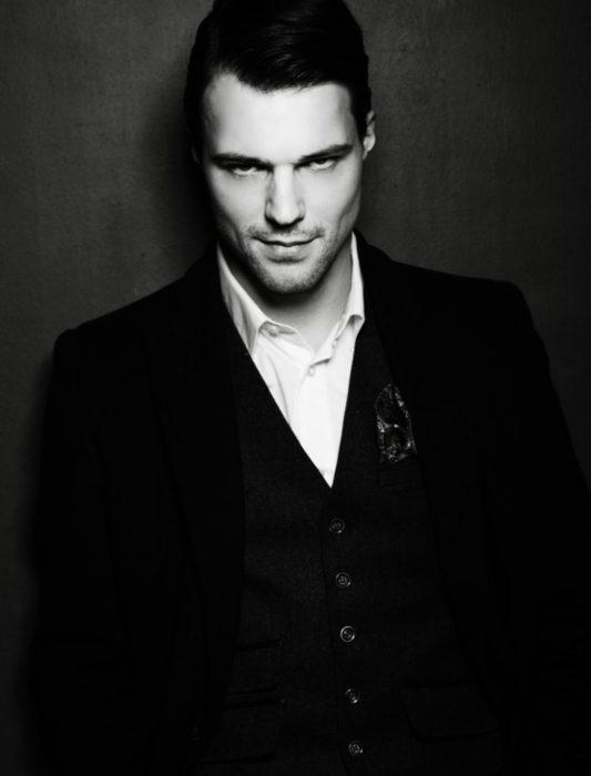 Hombre ruso guapo bien peinado, con traje negro y mirada seductora