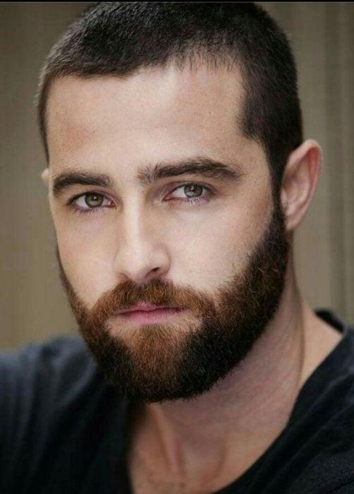 Hombre ruso guapo de cabello corto, barba y bigotes tupidos, y ojos verdes