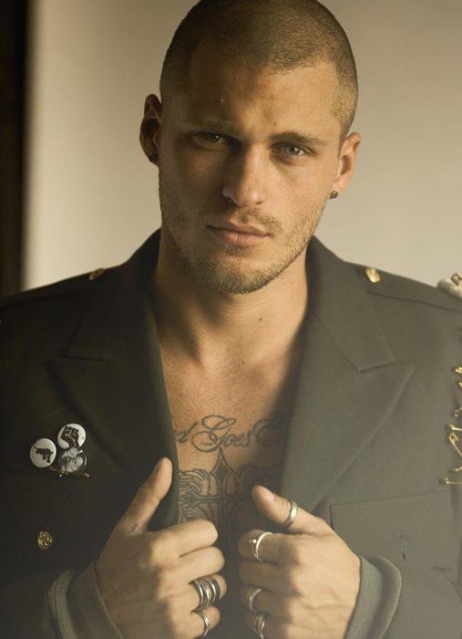 Hombre ruso guapo con tatuaje en el pecho y saco estilo militar