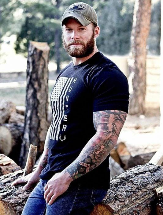 Musculoso hombre ruso guapo, rudo, con gorra, barba, bigote y tatuajes en el brazo