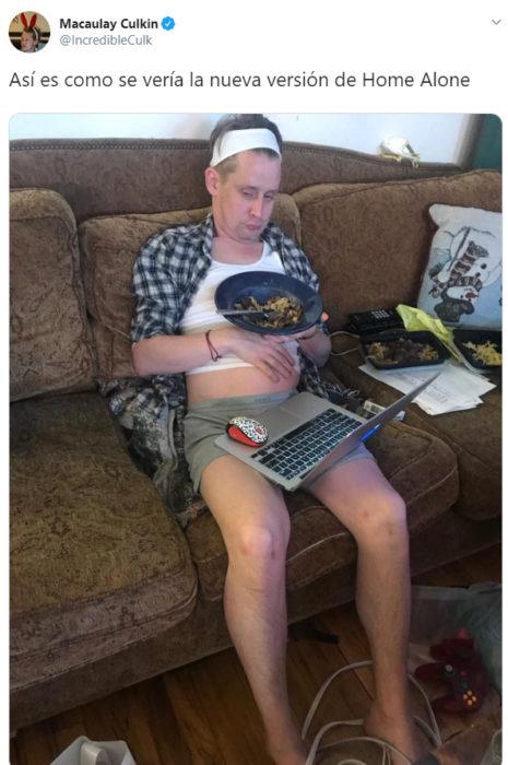 Macaulay Culkin sentado en un sofá con una computadora en sus piernas y comiendo sobras