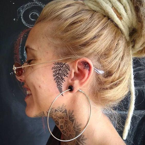 Chica de perfil mostrando su tatuaje de hoja en el oído